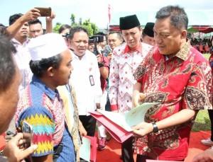 Gubernur Olly Dondokambey menyerahkan sertifikat tanah kepada masyarakat Bolsel.(Foto: hms)