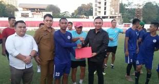 Victor Rarung dari Tim Lokal LIB Sulut menyerahkan bonus dari Gubernur Olly Dondokambey kepada Kapten Tim Sulut United Achmad Setiawan, disaksikan Pelatih Kepala Herry Kiswanto serta para pemain, di Stadion Klabat, Senin 22 Juli 2019.(Foto: ist)