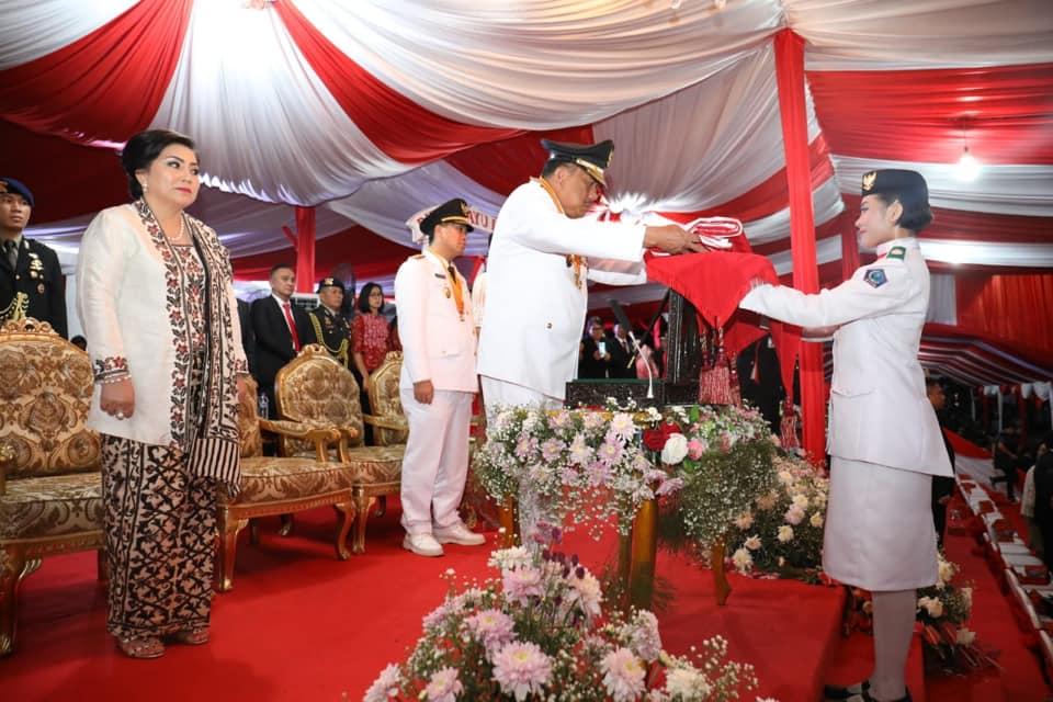 Gubernur Sulut Olly Dondokambey SE menerima kembali bendera merah putih yang dikibarkan siang hari pda peringatan Hari Kemerdekaan RI ke-74.(Foto: ist)