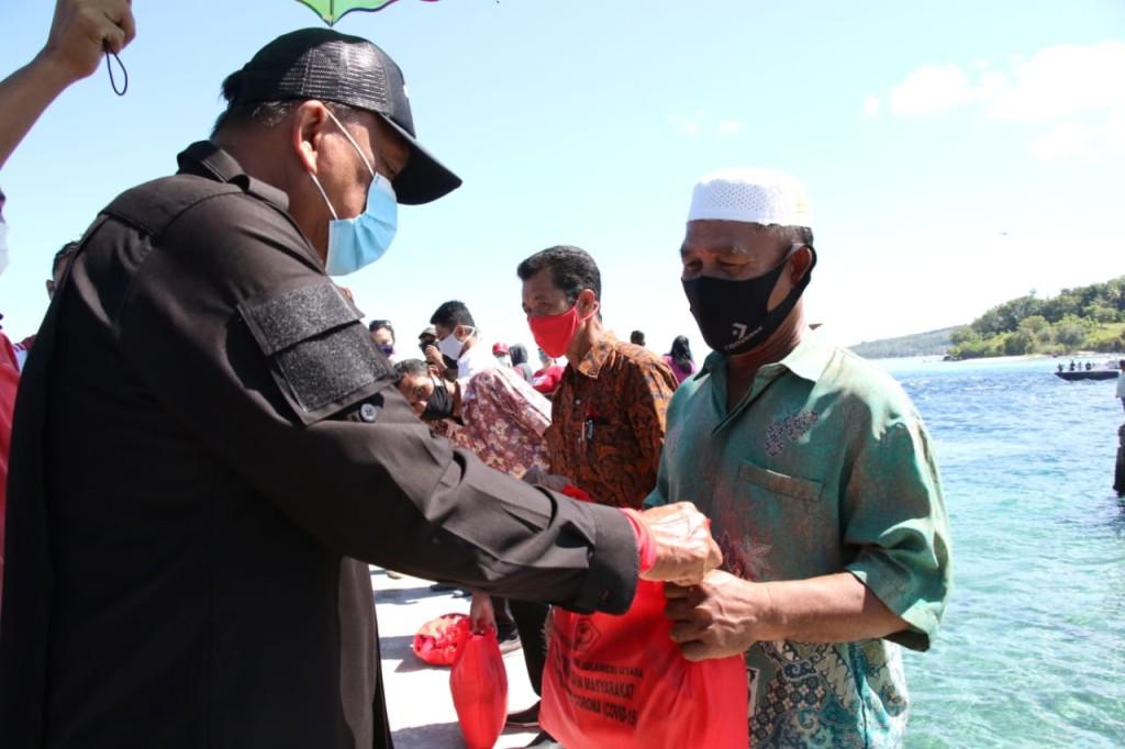 Gubernur Sulut Olly Dondokambey menyerahkan bantuan kepada warga di kepulauan di wilayah Minahasa Utara, Selasa 26 Mei 2020.(Foto: hbm)