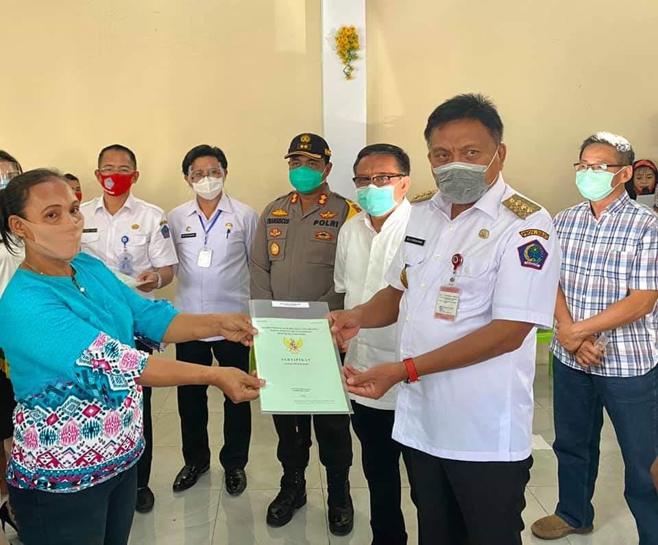 Gubernur Sulut Olly Dondokambey menyerahkan secara simbolis 1.400 sertifikat tanah program PTSL kepada eks transmigran di Bitung, Rabu 8 Juli 2020.(Foto: hbm)