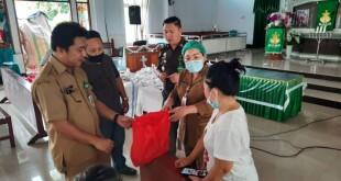 Kepala Dinas Sosial Pemprov Sulut dr Rinny Tamuntuan menyerahkan bantuan dari Pemprov Sulut di Minsel.(Foto: ist)
